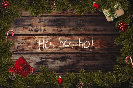 Christmas flatlay border with wrapped gifts, red balls, canes, bows, cone and green pine branches on the wooden background and Ho, ho, ho text