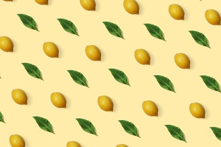 Summer exotic pattern with lemon and green leaves on the minimal background. Citrus wallpaper
