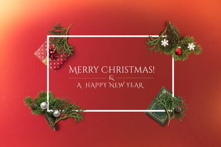 Merry Christmas and a Happy New Year holiday card with white border. Book, balls, pine and a red gift flatlay Фото со стока
