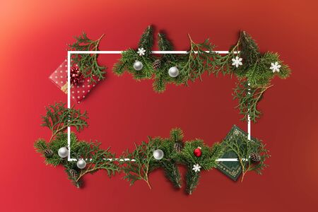 Merry Christmas and a Happy New Year holiday card with white border. Book, balls, pine and a red gift flatlay decoration with a copyspace Фото со стока