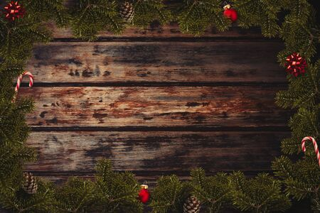 Christmas flatlay border with wrapped gifts, red balls, canes, bows, cone and green pine branches on the wooden background Фото со стока