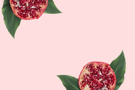 Red slices pomegranate with green leaves on the pink minimal background. Exotic fruit flatlay with copyspace