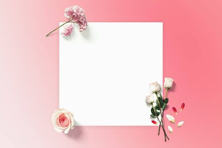 Spring flower flatlay with copyspace paper. Roses on the pink background top view. Holiday spring card