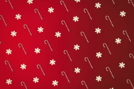 Christmas cane and snowflakes pattern top view on the red holiday background. Sweet wrapping design