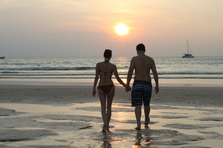Couple hand in hand in front of sunset on the beach, Thailand, Nai Harn Beach photo