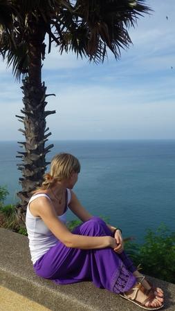 sitting young woman the Promthep Cape, Nai Harn Beach, Phuket Island, Thailand photo