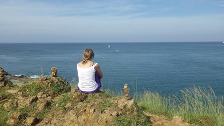 young woman sitting on the  Promthep Cape ,Nai Harn Beach, Phuket Island, Thailand photo