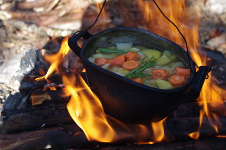 Stock Photo - vegetable soup in old tourist pot at fire place Summer trekking activity photo