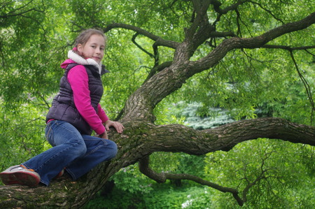 Stock Photo - A young girl sits on a tree at the background of a pond