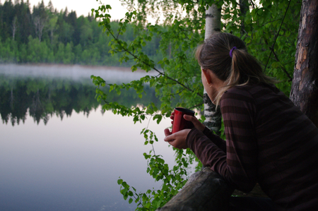 long lake: young woman drinking tea,  Lake Yastrebinoye - a pearl of Karelian land, Karelian Isthmus, Leningrad Oblast, Russia (Lake Yastrebinoye іs а 2 km long lake іn Priozersky District оf Leningrad Oblast, close tо the border w&#111