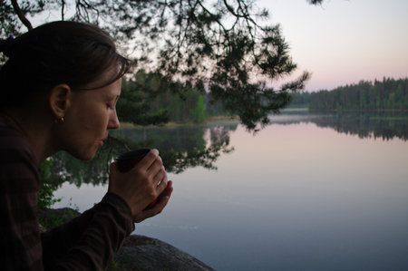long lake: young woman drinking tea  on the Lake Yastrebinoye - a pearl of Karelian land, Karelian Isthmus, Leningrad Oblast, Russia (Lake Yastrebinoye іs а 2 km long lake іn Priozersky District оf Leningrad Oblast, close tо the border