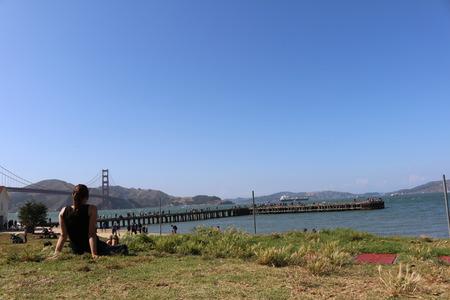 mammalia: young woman sitting in front of the Golden Gate Bridge, San Francisco, California, USA