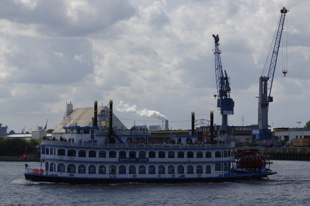 Paddle steamer Louisiana Star ferry in front of the Port of Hamburg with some container gantry cranes