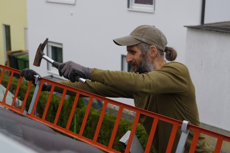 roofer: roofer or worker with a hammer on the roof