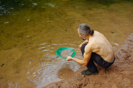 prospector: a man gold panning in a river with a sluice box Stock Photo