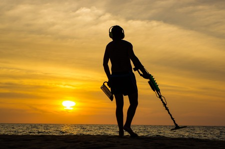 scavenge: a treasure hunter with Metal detector on sunset on the beach