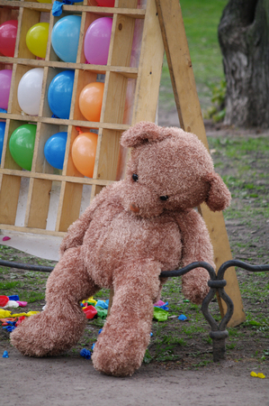 greenfield: sleeping lonesome teddy bear with balloons. Concept for missing you or forgive me. Stock Photo