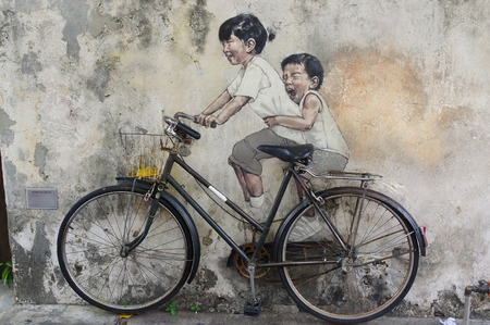 George Town, Penang, Malaysia - April 18, 2016: Little Children on a Bicycle street art mural by Lithuanian artist Ernest Zacharevic in Georgetown, Penang in Malaysia.