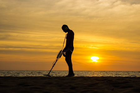 landmine: a treasure hunter with Metal detector on sunset on the beach