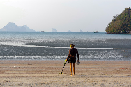 scavenge: a treasure hunter with Metal detector on sunrise on the beach