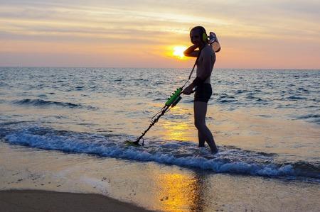 scavenge: a treasure hunter with Metal detector on the beach
