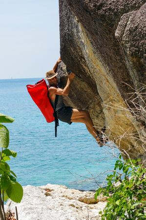 clambering: a strong and happy man climbing on high rock over the sea with a hut and a red seabag. Stock Photo