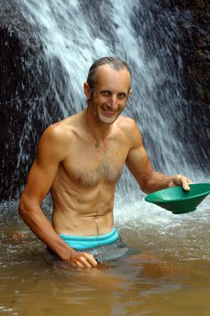 prospector: un hombre lavado de oro en un río con una caja de la esclusa