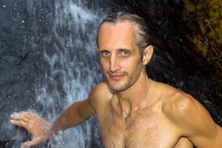 a man taking a relaxing shower under a waterfall outside Stock Photo