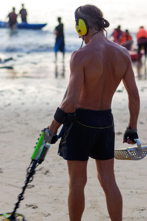 a treasure hunter with Metal detector on the beach