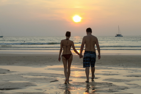 looking away from camera: couple walking on beach at the sunset Stock Photo