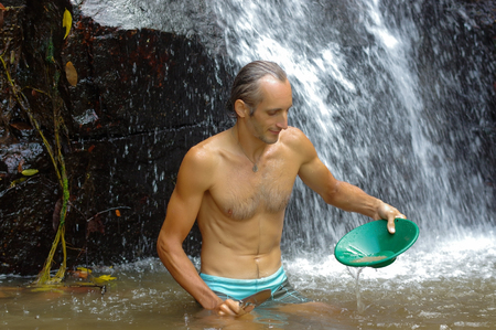 a man gold panning in a river with a sluice box Stock Photo
