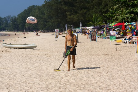 landmine: a treasure hunter with Metal detector on the beach