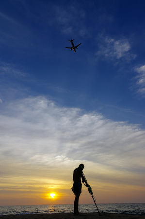 a treasure hunter with Metal detector on sunset on the beach, with a plan in the sky. Stock Photo