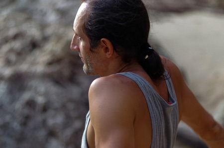 graying: a portrait middle aged man with long hair sideview, outside with rock on background