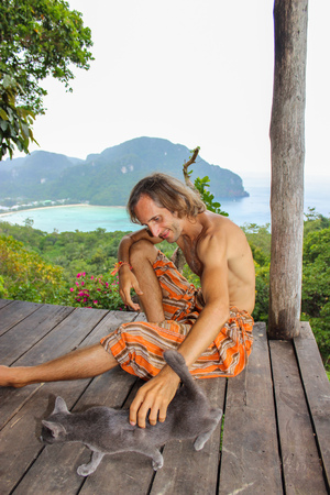 british man: a handsome relaxing man stroking gray british shorthair cat with Krabi seascape background