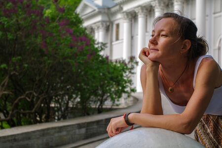 a portrait of young charming relaxing brunette woman with head laid on her arms at summer green park. Stock Photo