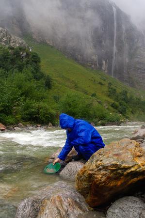 prospector: un hombre lavado de oro en un río con una caja de la esclusa durante la lluvia