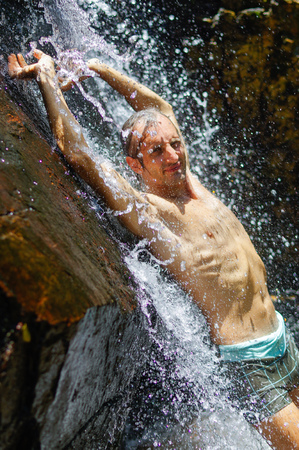 armpits: a man taking a relaxing shower under a waterfall outside Stock Photo