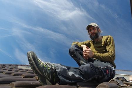 roofer: Roofer resting on top of a roof