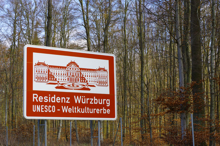 signposted: a red highway sign with a ilustration of historic place in Bavaria, Germany, part of the UNESCO World Heritage Site - Residenz Wuerzburg UNESCO Kulturerbe - in German