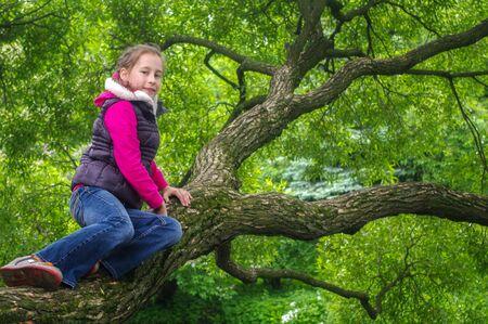 adolescencia: una niña juguetona divertida sube en un árbol en el parque. niños al aire libre. vacaciones en el parque de verano