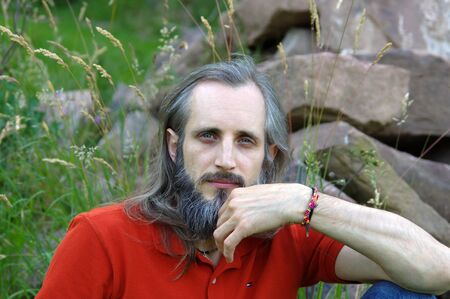 a bearded happy man sitting in a green background on sunny day, potrait
