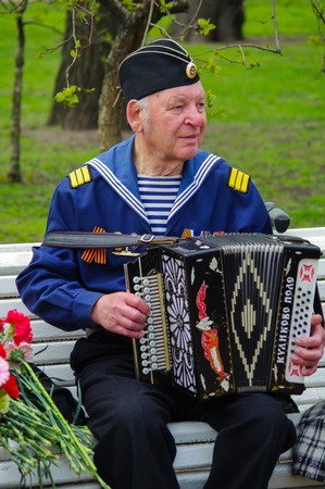 pleasent: ST.PETERSBURG, RUSSIA - MAY 9, 2014: A very pleasent veteran plays accordion on the 69-th anniversary of the victory in the World War II on May 9, 2013, St.Petersburg, Russia
