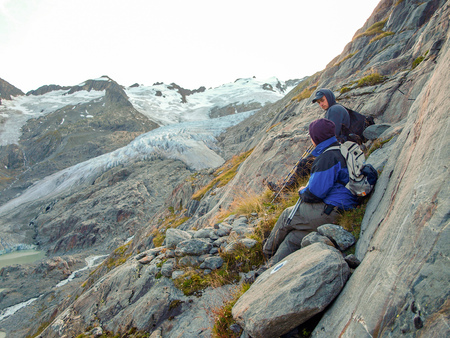 few Young hikers trekking or resting in the alps, Switzerland, with glaciers mountains in the background