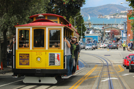 San Francisco, California - Mai 23, 2015: Lot Tourists riding on the iconic cable car, blue sky day at top of Hyde Street view overlooking the bay water and Alcatraz prison