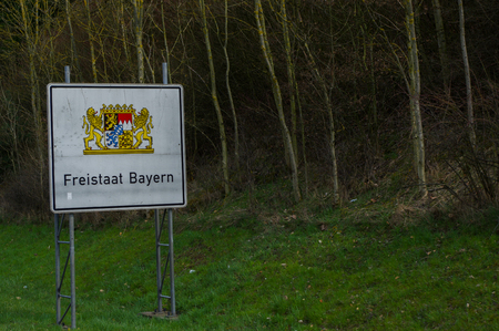 a white highway border sign with coat of arms Bayern, Germany, translation in English: Freestate Bavaria