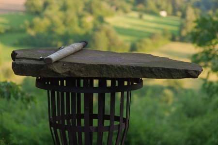 holzbriketts: Empty portable BBQ grill in front of a fresh green summer landscape Lizenzfreie Bilder
