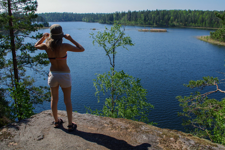 a female hiker standing on rocky trail and waching azure amazing colors mountain forest lake on background
