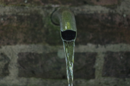 Close up of running water from a tap with a stone background