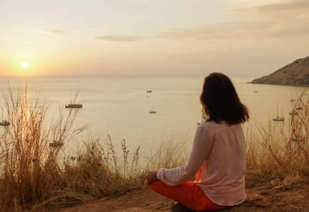 a Young girl sitting in yoga lotus meditation position in front to seaside on the rocks an watching the sun goes down in a golden hour. sunset over sea. Banco de Imagens